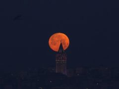 ISTANBUL, TURKEY - JANUARY 31: Full moon is seen over Galata Tower in Istanbul, Turkey on January 31, 2018. Emrah Yorulmaz / Anadolu Agency